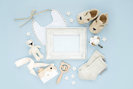 Photo frame with set of clothes and accessories fot newborn boy. Toys, socks and baby slippers with bib on blue background. Mock up tor text.  Flat lay, top view