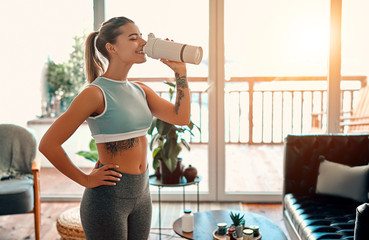 Athletic woman in sportswear drinking a protein shake or a bottle of water at home in the living room. Sport and recreation concept.