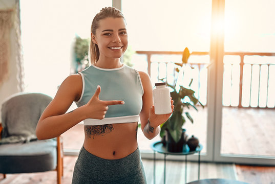 Athletic woman in sportswear holds a jar of protein in her hand and shows a finger gesture at home in the living room. Sport and recreation concept.