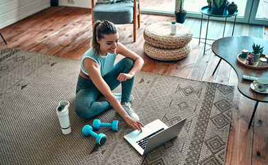 A sporty woman in sportswear is sitting on the floor with dumbbells and a protein shake or a bottle of water and is using a laptop at home in the living room. Sport and recreation concept. Wall mural