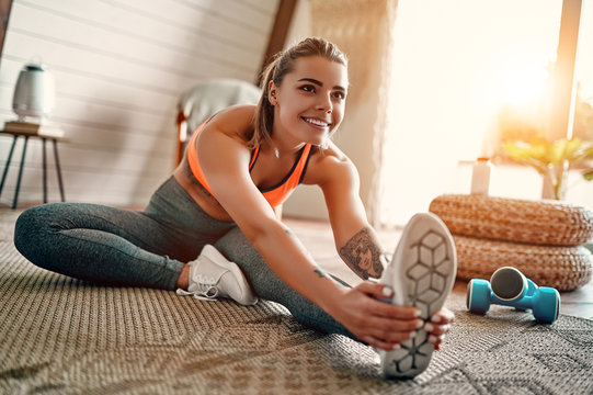 Athletic woman in sportswear doing fitness stretching exercises at home in the living room. Sport and recreation concept.