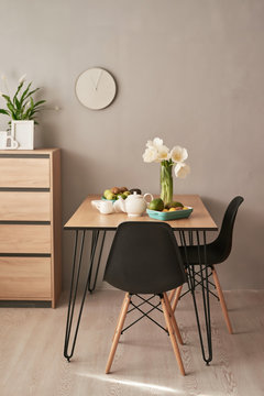 Loft style dining room. Dining table with chairs. Mock up interior photo. Black chairs at dining table in bright dining room with flowers. Kitchen island and table in contemporary apartment interior