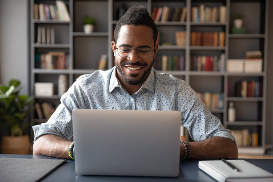 Young smiling african american businessman looking at laptop screen.