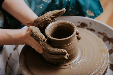 Close up mud covered hands of adult woman making clay pot on potter's wheel