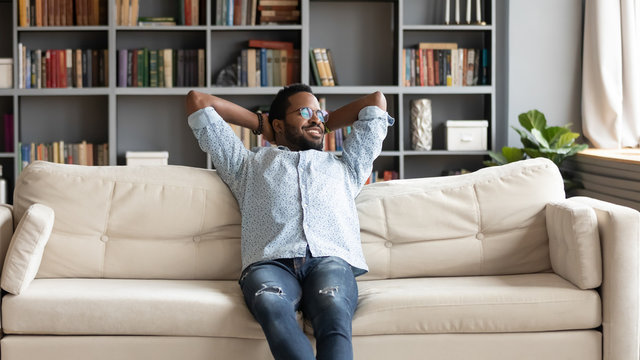 Peaceful young african american man stretching back, relaxing on couch.