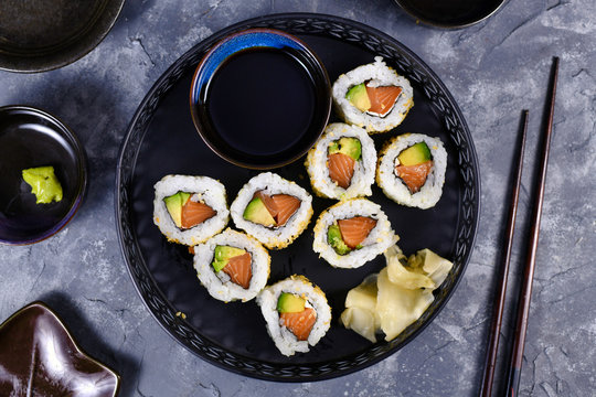 Sushi california rolls filed raw salmon fish, avocado, cream cheese and topped with sesame