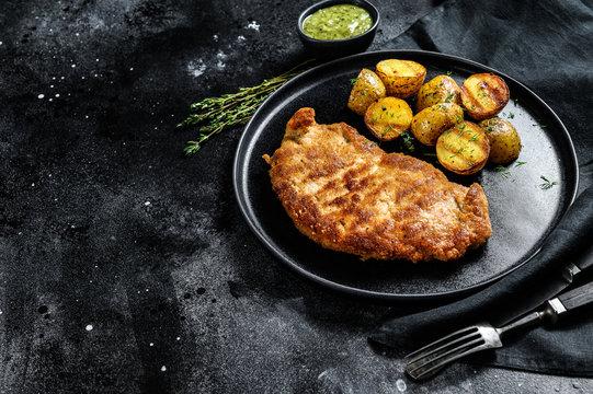 Breaded german weiner schnitzel with potatoes. Black background. Top view. Copy space