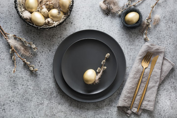 Easter table setting with black and golden eggs on grey table.  Top view.
