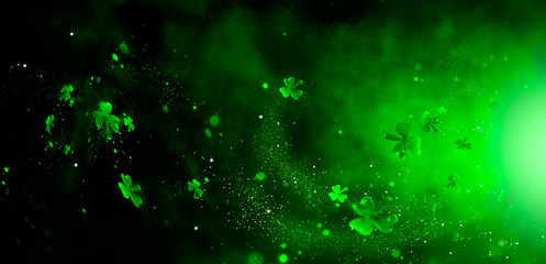 St. Patrick's Day abstract green background decorated with shamrock leaves. Patrick Day pub party celebrating. Abstract Border art design magic backdrop. Widescreen clovers on black with copy space Wall mural
