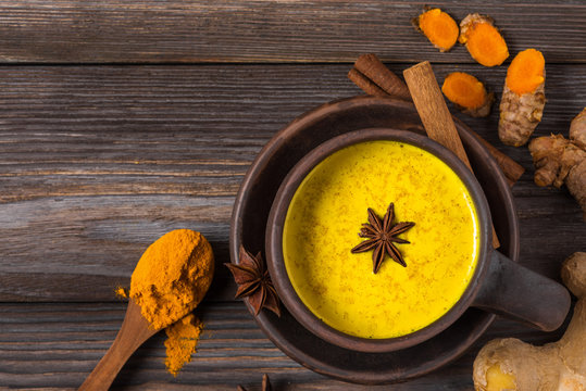Traditional Indian drink turmeric latte or golden milk with cinnamon, ginger, anise, pepper and turmeric. top view