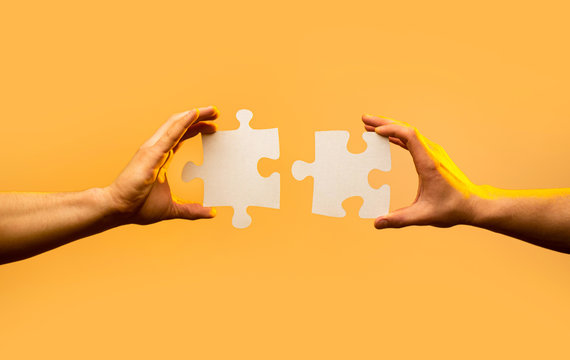 Closeup hand of connecting jigsaw puzzle. Business solutions, success and strategy concept. Two hands trying to connect couple puzzle piece on yellow background. Holding puzzle. Teamwork concept