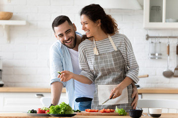 Smiling couple stand in kitchen cooking meal together