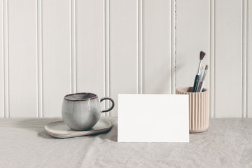 Blank paper card, invitatation mockup. Artistic stationery scene with paint brushes, pencils in...