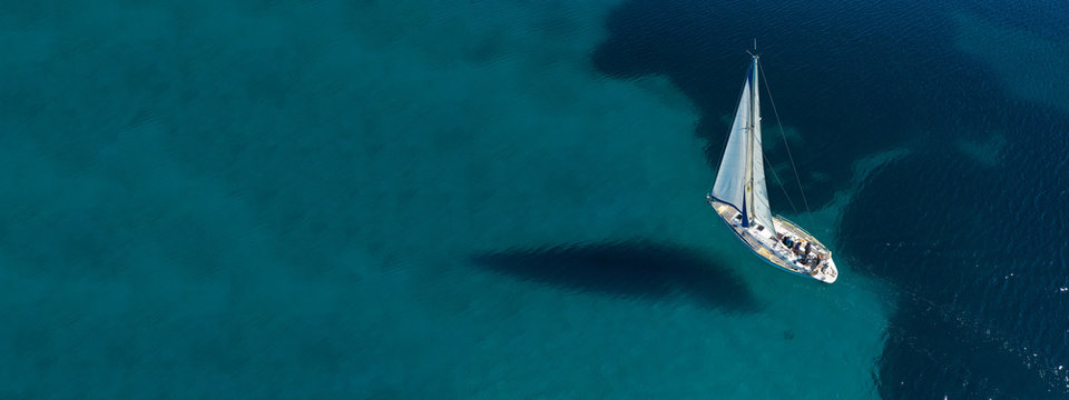 Aerial drone ultra wide photo of beautiful sail boat sailing in tropical exotic bay with emerald clear sea