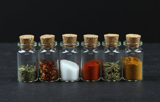 Photo of a line of glass vials with cork bungs filled with different spices
