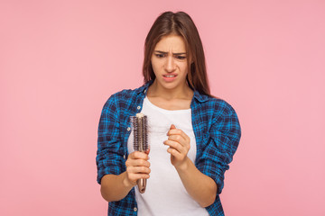 Portrait of stressed brunette woman in casual style clothes looking at unhealthy hair on brush, checking dandruff, upset by hair loss problem, alopecia. indoor studio shot isolated on pink background Fotobehang