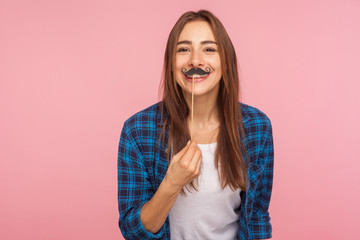 Portrait of cheerful playful girl in checkered shirt holding fake curled mustache on stick and smiling to camera, having fun, wearing masquerade accessory. studio shot isolated on pink background