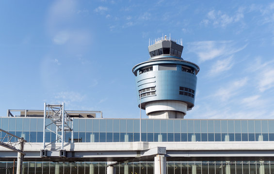 LaGuardia airport control tower. Cylindrical shape structure. Blue sky and wispy cloud background..