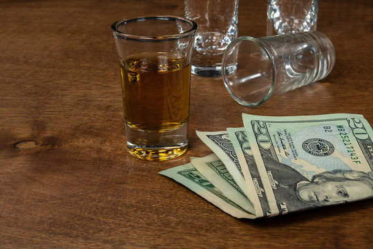 shot of whiskey and empty shot glasses on wood with American money