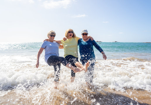 Group of three senior women walking having having fun on beach. Friendship and healthy lifestyle