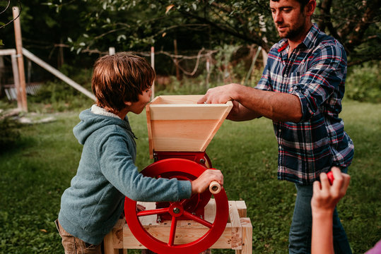 A family pressing apples to make cider
