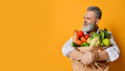 Keuken foto achterwand Kruidenierswinkel Cool old mature senior man with gray beard shopping hold grocery shopping bag with healthy organic vegetables on yellow