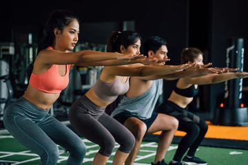 Close-up of group of athletic young Asian people in sportswear doing squat and exercising at the...