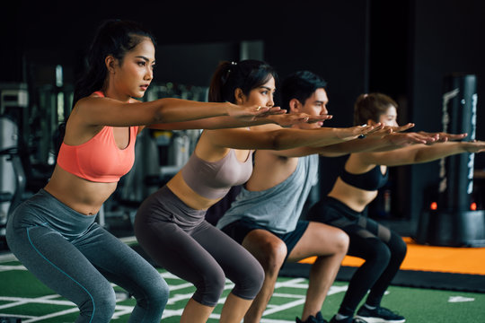 Close-up of group of athletic young Asian people in sportswear doing squat and exercising at the gym. Intense workout and healthy lifestyle concept
