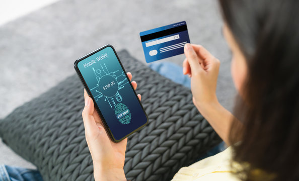 Woman holding smartphone and credit card with scanning biometric fingerprint for approval to access for payment mobile banking on application wallet.