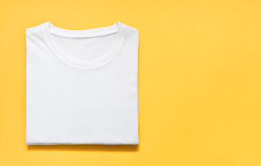 top view of folded white color t-shirt on yellow background, copy space, flat lay