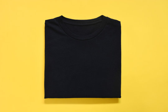 top view of folded black color t-shirt on yellow background, copy space, flat lay