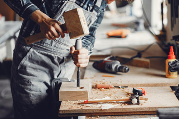 Fototapeta A man carves a tree. The carpenter works with a hammer in a studio. An engineer provides a tree shape obraz