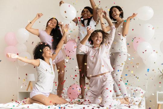 Happy diverse girls wearing pajamas throwing confetti, having fun