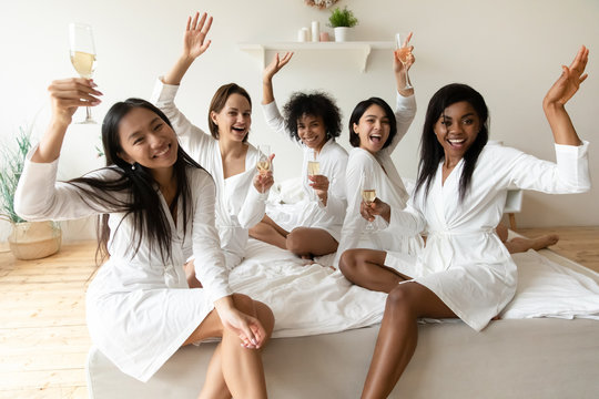 Portrait happy diverse girls holding champagne glasses looking at camera