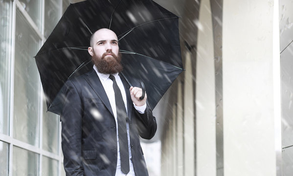 A bald bearded man in a suit