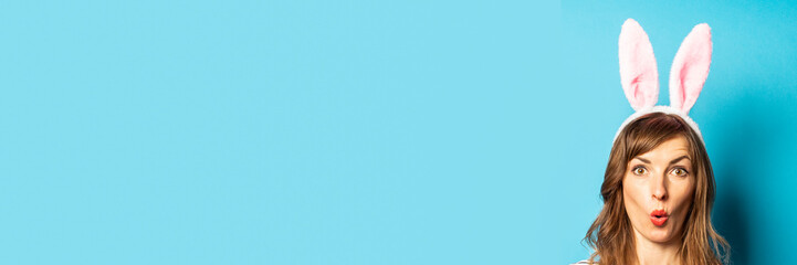 Young woman with rabbit ears looks out over a blue background. Easter concept, surprise, hide and seek. Banner
