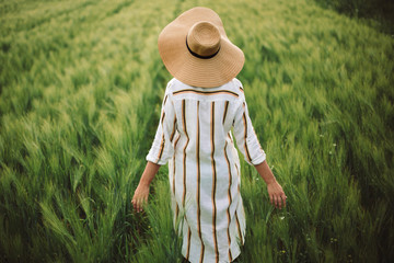 Woman in rustic dress and hat walking in green field of barley. Atmospheric authentic moment. Stylish girl enjoying peaceful evening in countryside. Copy space. Rural slow life