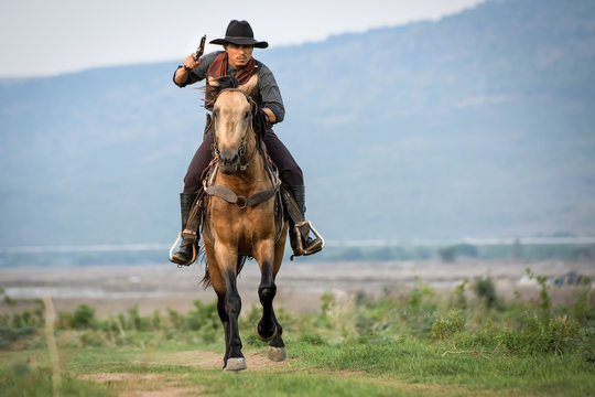 Cowboy man riding horse shooting