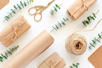 Set of materials for packing holiday gifts. Kraft paper, jute twine, scissors, boxes and twigs of green eucalyptus on white background. Holiday zero waste and eco-friendry concept. Top view Flat lay