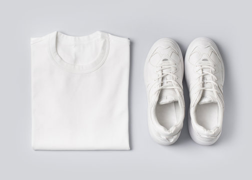 Fashion female clothes on white background. Basic T shirt and sneakers.