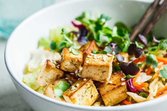 Fried tofu salad with sprouts and sesame seeds in white bowl. Vegan food, asian food concept.
