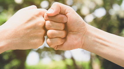 Teamwork in the nature concept,Which Young man fist bump  in the nature of bokeh background,
