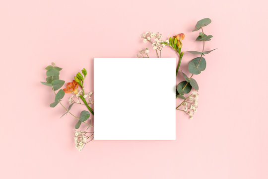 Blank paper card mockup with frame made of flowers and eucalyptus. Floral composition with copy space on a pink pastel background.