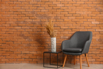 Soft armchair and table with vase near brick wall in room