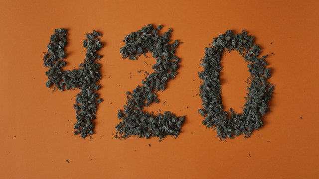 Top view close up sign 420 made from a hemp buds on red background