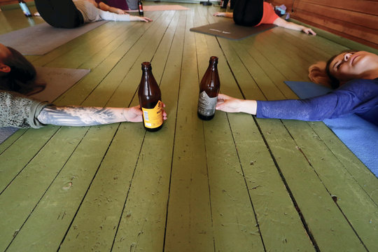 People hold bottles as they perform beer yoga in Riga