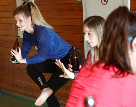 Trainers Oficiere and Tamme hold bottles as they perform beer yoga in Riga