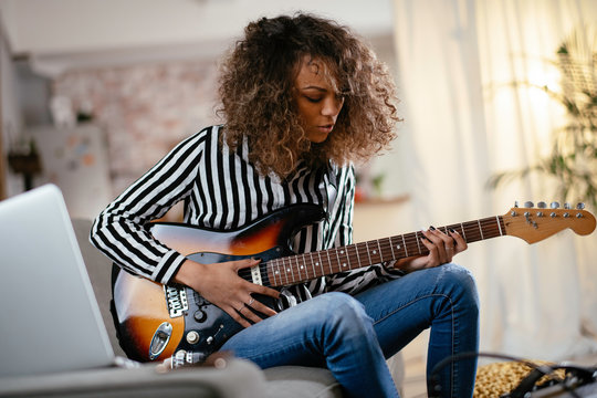 African woman with guitar. Beautiful woman playing guitar.