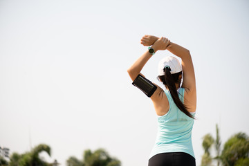 Young fitness woman runner stretching arm before run in the park. Outdoor exercise activities concept.