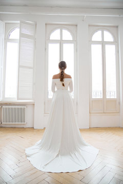 Beautiful slender blonde in the evening sun in a long white dress near a large window. Perfect hair and makeup for the bride, a new collection of wedding dresses
